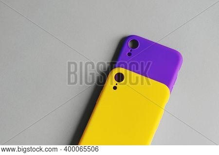 Two Silicone Cases For The Smartphone Lie On A Gray Background. Yellow And Lilac Covers For The Smar