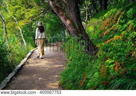 Young woman traveler walking on wooden path trail in Plitvice Lakes National Park, UNESCO natural world heritage and famous travel destination of Croatia