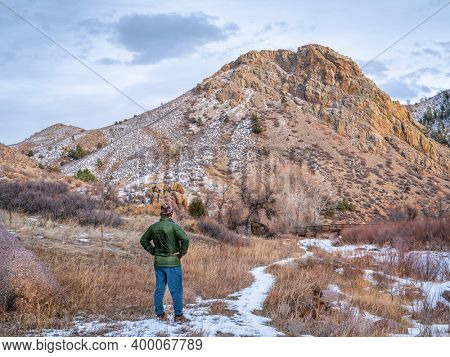 hiker and Eagle Nest Rock with a frozen North Fork of Cache la Poudre River in northern Colorado at Livermore near Fort Collins, winter scenery