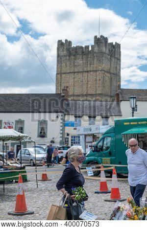 Richmond, North Yorkshire, Uk - August 1, 2020: A Woman Wearing A Homemade Face Mask Queues To Buy F