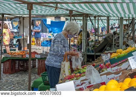 Richmond, North Yorkshire, Uk - August 1, 2020: A Woman Wearing A Face Mask Picks Fruit And Vegetabl