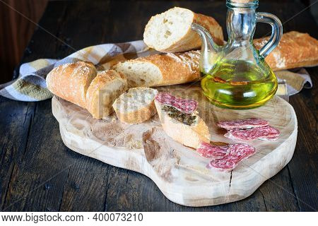 Some Slices Of Spanish Sausage Fuet, White Bread And Olive Oil On The Natural Wooden Kitchen Board.