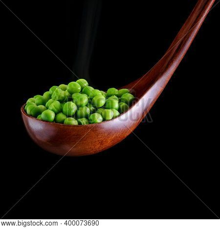 Big Wooden Spoon With Green Broiled Peas On The Black Background.