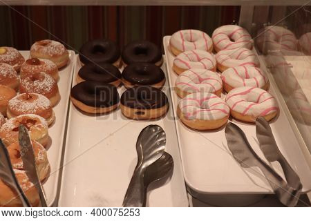 Two Different Iced Donuts On A Tray On A Cruise Ships Buffet.