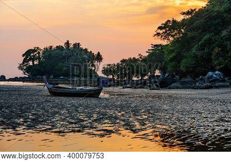 Traditional Thai boats at the beach at sunset time. Nai Yang beach. Phuket. Thailand