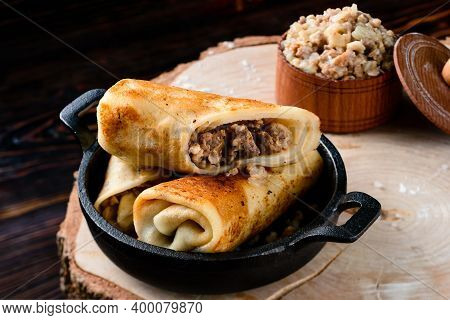Homemade Minced Meat Rolled Crepes Served In Cast Iron Pan On Rustic Wooden Table, Crepes Stuffed Wi