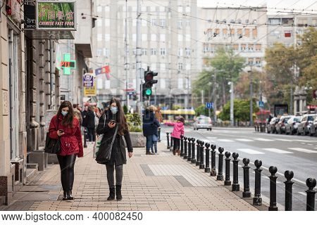 Belgrade, Serbia - October 17, 2020: Two Young Women Wearing A Respiratory Face Mask Checking Apps O