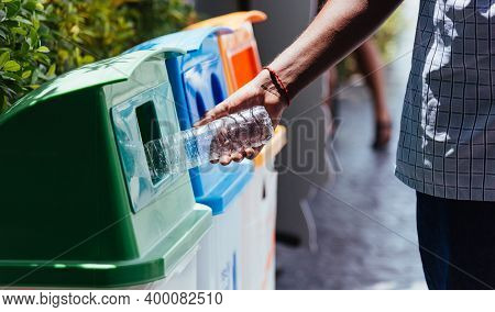 Selective Focus Close Up The Man Black Hand Throwing An Empty Plastic Water Bottle In The Recycling