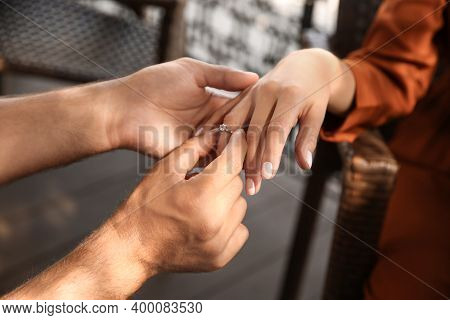 Man Putting Engagement Ring On His Girlfriend's Finger Outdoors, Closeup