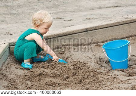 Child Baby In Sandbox Playing With Beach Toys. Girl Toddler Digging Sand And Building Sandpie. Kid H