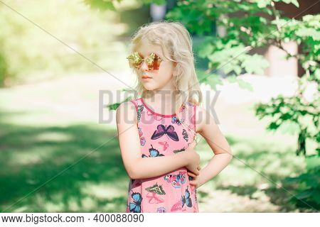 Young Girl Posing In Fancy Pink Pentagonal Shaped Sunglasses Outdoor. Cute Serious Pensive Stylish C