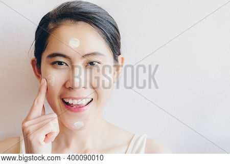 Portrait Of Asian Woman Marking And Applying Cream Concealer On Her Facial Skin. Concealer Is A Type