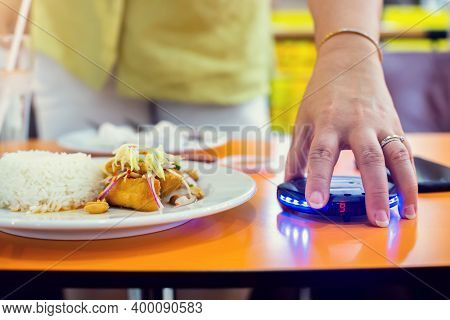 Wireless Queue Caller Machine In Hand Of Customer With Food.