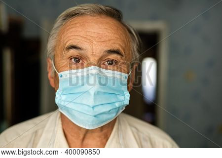 Coronavirus Quarantine. Senior Man Wearing Protective Mask Behind The Window Stay At Home To Avoid C