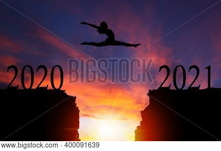 2021 New Year Concept With Silhouette Of Courageous Girl Jumping Over Cliff With Dramatic Sunset Or