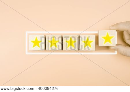 Business Service Rating , Satisfaction Concept. Hand Arranging Symbol With Star Icon On Wood Cube Bl