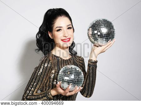Sexy disco party woman with lond brunette hair. Sequin party dress, disco balls, bright makeup.