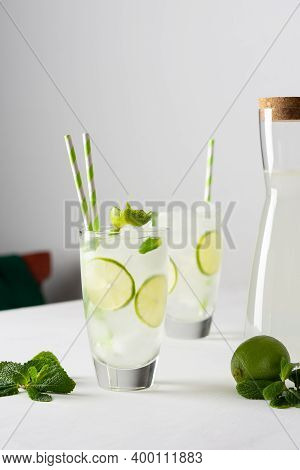 Refreshing Cold Drinks With Lime And Mint, Glasses With Lemonade And Ice And Straws, Jug With Drink