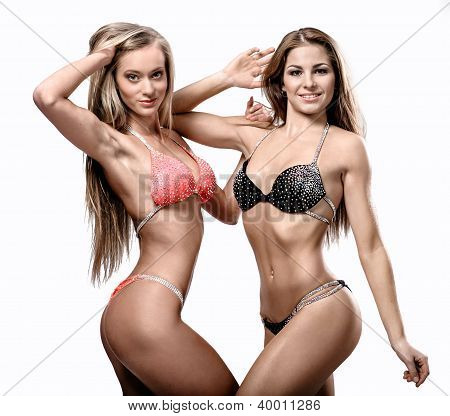 Two Attractive Athletic Girl Wearing Bikini Posing Over White Background