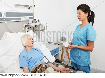Geriatric Nurse Measures The Pressure Of A Senior Woman Patient Who Is Lying On A Hospital Bed. Prev