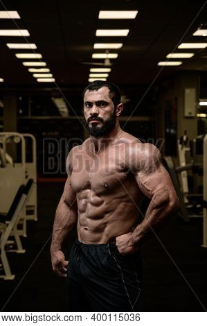 Strong Young Bearded Caucasian Man With Perfect Sport Physique Body In Dark Fitness Bodybuilding Gym