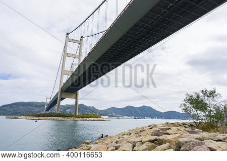 Hong Kong - November 2020 : Tsing Ma Bridge between Ma Wan island and Tsing Yi island. A woman is fishing under the bridge. Low Angle View