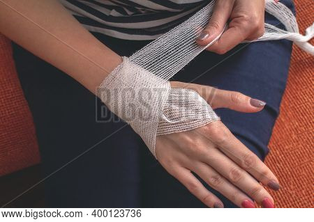 Young Caucasian Woman Is Bandaging Her Wounded Palm And Wrist Indoors. Wraps The Hand With A Gauze B