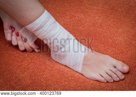 Bandaged Female Lower Leg With Gauze Bandage. Bandaged Shin Closeup Against The Background Of The Su