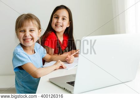 Cool Online School. Kids Studying Online At Home Using A Laptop. Cheerful Young Little Girls Using L