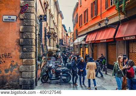 Bologna, Italy, March 17, 2019: People Are Walking Down Typical Italian Street With Buildings With B