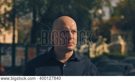 Close Up Of A Hairless Handsome Male Face With Green Eyes Looking Up On Blurred Street Background. S