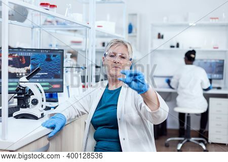 Senior Scientist In Modern Laboratory Holding Genetic Sample On Laboratory Glass. Elderly Researcher