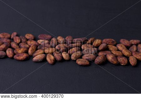 Unpeeled Raw Brown Cocoa Beans In Heap Lie On Black Modern Concrete Background. Flat Lay, Mock Up, C