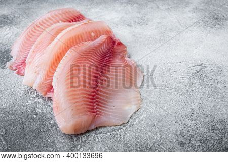 Tilapia Fish Skinless Meat, On Gray Background With Copy Space For Text
