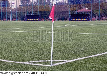 Part Of A Football Field With Green Grass On A Lawn With White Markings And A Red Flag On The Corner
