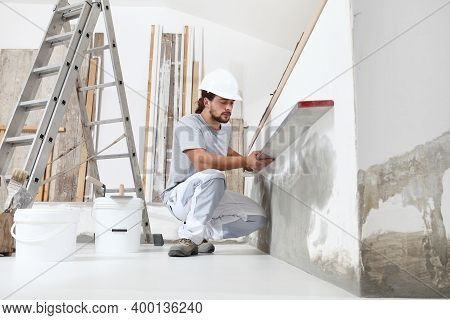 Construction Worker Plasterer Man Looks At The Spirit Level And Checks The Wall In Building Site Of