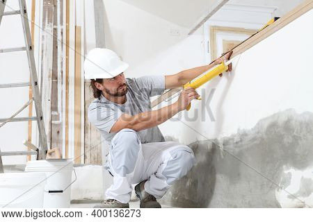 Construction Worker Plasterer Man Uses Caulking Gun In Building Site Of Home Renovation With Tools A