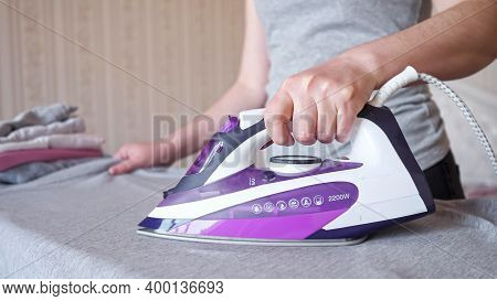 Hardworking Woman Holding Modern Purple Electric Iron Irons Fast And Carefully Grey Shirt After Laun