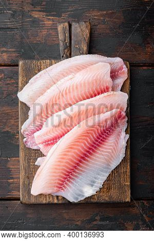 Tilapia Fish Skinless Meat, On Dark Wooden Background, Top View