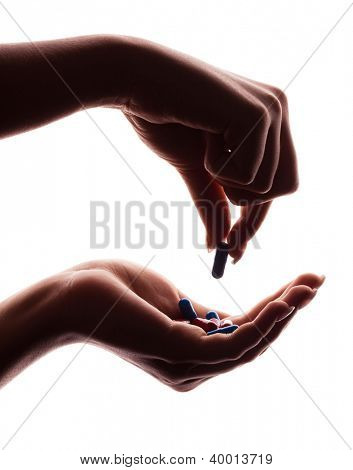 hands of a woman holding pills, isolated against white background