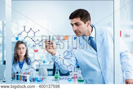 Scientists Drawing Chemical Formulas On Clear Board In Science Laboratories.