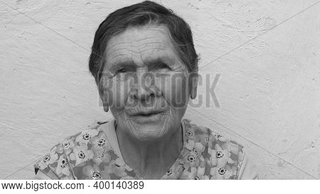 Black And White Authentic Portrait Of 80 Years Old Lady Of Mixed Ethnicity. Wrinkled Face Of Elderly