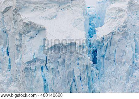 Deep Blue Crack In A Glacier In Antarctica. A Break In The Glacier. Global Warming.