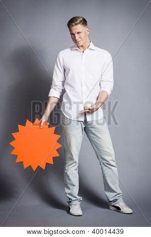 Confident handsome man pointing finger at blank panel with space for text, advertising, announcement, sale etc. isolated on grey background.