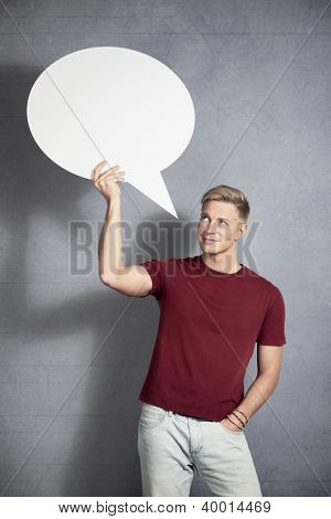 Good idea: Friendly handsome man looking at white blank speech balloon with space for text, while holding it, isolated on grey background.