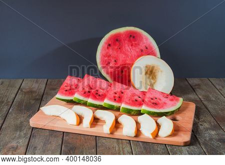 Slices Of Watermelon And Melon And Half Of Watermelon And Melon On Wooden Table. Selective Focus. Vi