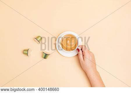 Top View Of Coffee Capsules And Woman Hand Holding Coffee Cup Over Beige Background With Copy Space.