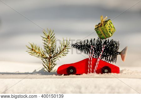Red wooden toy car with Christmas tree and christmas gift box on snow