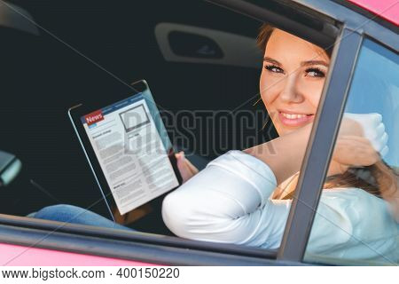 Woman In A Car With A Tablet In Hands, Reading News