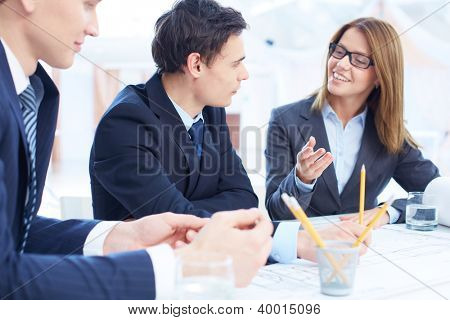 Image of confident businessman listening to his partner while looking at her at meeting